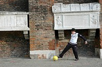 Venice (Italy), boy playing soccer in front of an ancient church