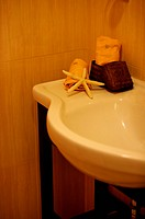 Corner of a basin, with hand towels and a starfish decoration on it