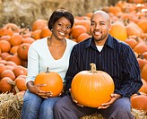 Happy smiling couple sitting on hay bales and holding pumpkins at outdoor market.