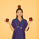 Asian Chinese mid-adult female doctor holding two red apples in hands and balancing one on head against yellow background smiling and looking at viewe...