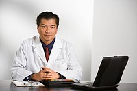Asian American male doctor sitting at desk with charts and laptop computer looking at viewer.