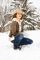 Caucasian young adult female looking at viewer while kneeling in snow with snowball and wearing straw cowboy hat.