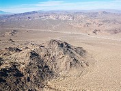 Aerial view of remote California desert with mountain range in background