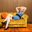 Attractive Caucasian woman laying on retro couch holding hair up.