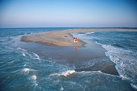 Birds eye view of couple on sandbar at Bald Head Island, North Carolina during sunrise