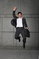 businessman holding briefcase, jumping with arm raised