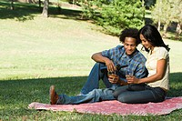Couple having romantic picnic in park drinking wine