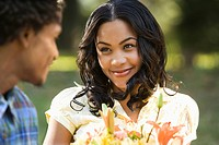 Woman holding flower bouquet smiling at man