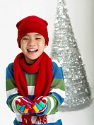 boy dressed in winter clothes in front of christmas tree
