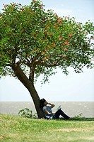 Young woman sitting under tree, reading book