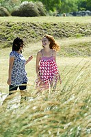 Two young women walking and laughing together outdoors