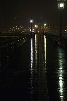 Elevated pedestrian walkway wet after rain at night, above Brooklyn Bridge, New York City