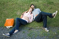 Young couple lying together on grass, high angle view