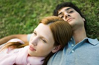 Young couple lying together on lawn, portrait