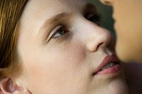 Young woman gazing at man's face, extreme close_up