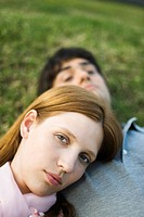 Young couple lying on ground, woman resting head on man's chest, looking at camera