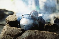 Tea steeping in cup placed atop cast iron pot cooking on traditional stove (thumbnail)