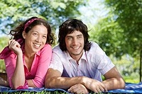 Young couple lying on blanket in park