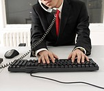 Office Worker Typing with Keyboard While on Phone