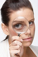Mid adult woman looking through magnifying glass (thumbnail)