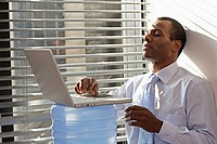 Mid Adult Man Using Laptop on Water Cooler