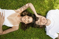 Young couple lying on lawn, woman touching man's head directly above