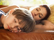 Mother and son sleeping on sofa