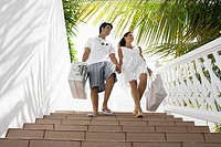 Young couple walking down steps with luggage