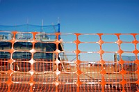 Orange safety plastic netting surrounding a construction site