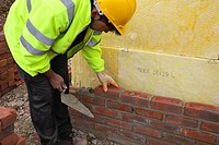 Bricklayer with trowel building a cavity wall