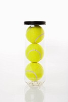 New tennis balls stacked in plastic container