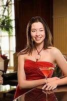 Taiwanese mid adult woman in red dress smiling and standing at bar with drink (thumbnail)