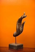 Carved hand sculpture from Thailand against orange wall (thumbnail)