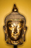 Bronze Buddha head from Thailand against yellow wall