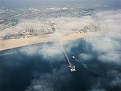 Aerial view of clouds covering beachfront and fishing pier in southern California