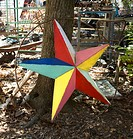 Colorful painted star made of metal leaning against tree (thumbnail)