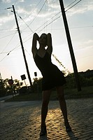 Silhouette of Caucasian mid_adult blonde woman wearing little black dress posing in street