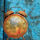 Old weathered alarm clock against rusty blue metal background