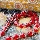 Close up of red bead necklace against pattern mosaic