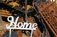 Metal garden decoration of word Home next to rusted metal objects