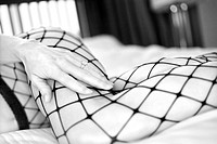 Close up of Caucasian woman in fishnet stockings on bed