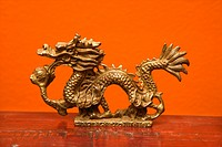 Chinese Taoist wisdom brass dragon statue against orange wall