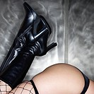 Caucasian female buttocks and legs in black boots