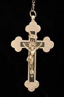 Close up of crucifix pendant against black background