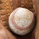 Close up of baseball resting in baseball glove
