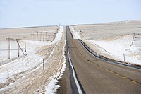 Road over rolling hill landscape with snow and power lines