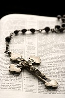 Rosary with crucifix lying on open Bible