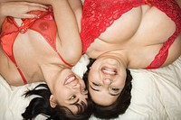 Young Caucasian women in sexy red lingerie lying in bed smiling