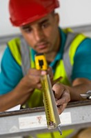 Builder measuring studs with tape measure
