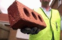 Bricklayer holding a red brick